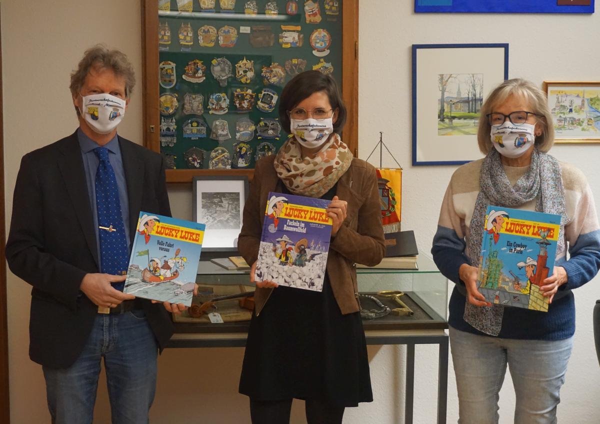 La présidente du comité de jumelage, Regina Haunhorst (à droite), présente les trois tomes de Lucky Luke accompagnée de son adjoint Thomas Fricke et de la maire du district, Lara Mohn